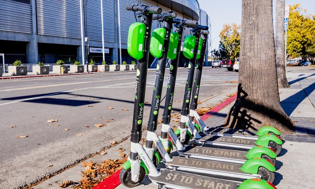 Lime Scooters lined up on a sidewalk in downtown.