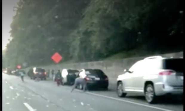 Drivers stop on I-285 to collect cash that fell out of an armored truck. (Photo: WSBTV.com via AJC.com)