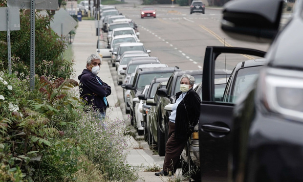 Two people wear masks to protect themselves from the coronavirus as they wait in a long line of cars at a California food bank.