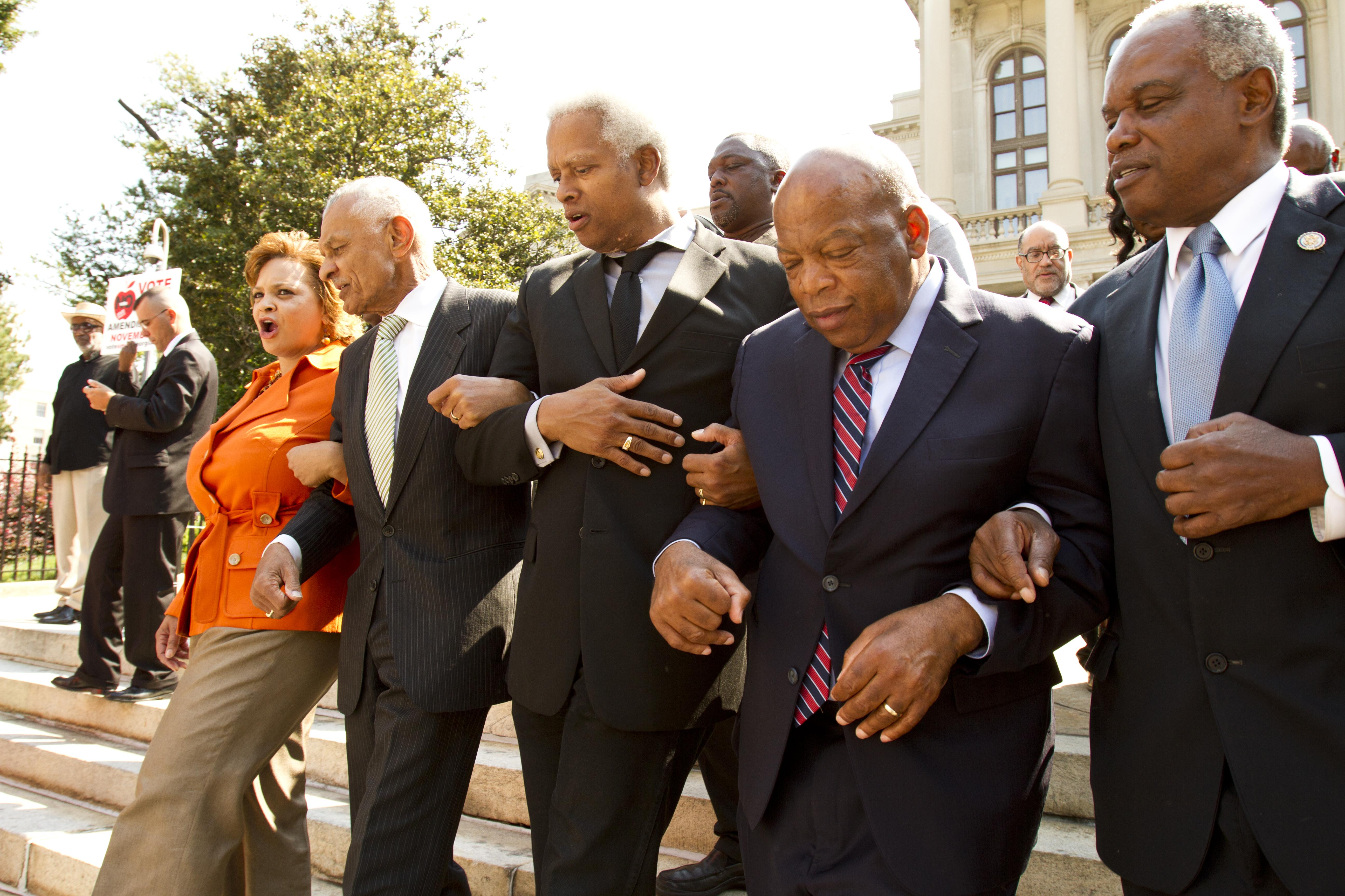 Five people marching arm-in-arm: Deborah Scott, Rev. C.T. Vivian and U.S. Reps. Hank Johnson, John Lewis and David Scott. Photo By John Disney 9-25-2012
