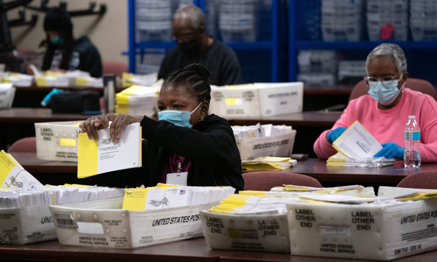Election officials wearing protective masks sort empty absentee ballot envelopes for the 2020 Presidential election by precinct for storage at the Dekalb County Voter Registration and Elections Office in Decatur, Georgia, U.S., on Thursday, Nov. 5, 2020. Republicans are watching with alarm and anxiety as the race narrows in Georgia, where Trump's lead slipped to about 18,500 votes throughout the count that continued into Thursday. Photo: Elijah Nouvelage/Bloomberg
