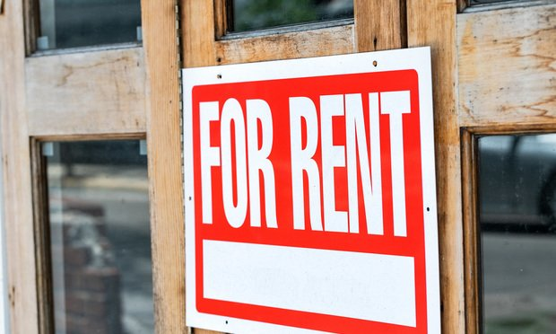 Closeup of red, white for rent sign attached, hanging on wooden apartment, house, home, building door with glass windows