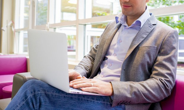 Young businessman in jeans using laptop.