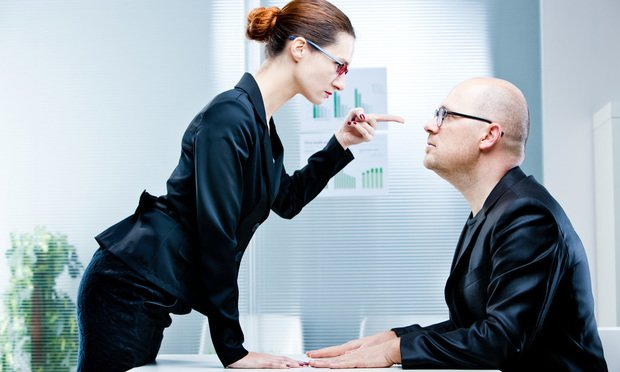 business woman pointing out a business man reproaching him at work in an office