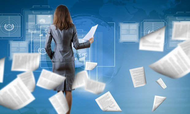 businesswoman surrounded by papers flying