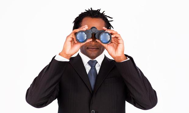 Afro-american businessman looking through binoculars.