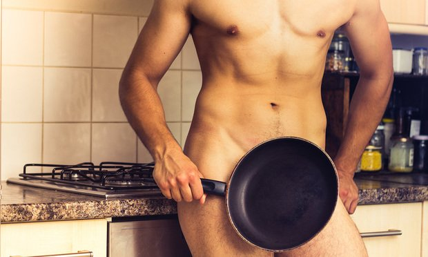 naked man in kitchen with frying pan covering private area