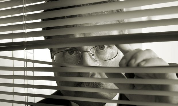 man peeking behind blinds.