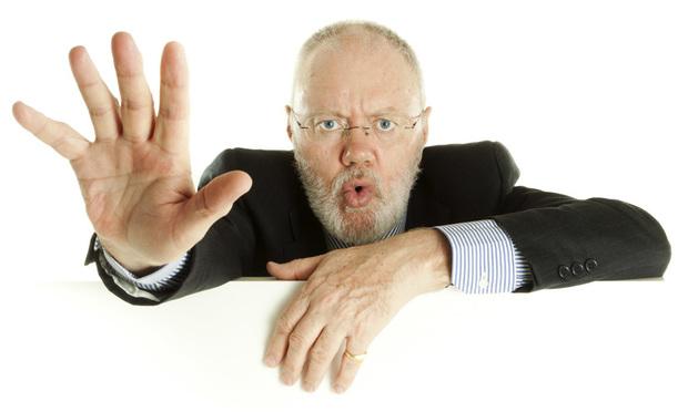 Elder businessman gesturing to stop.