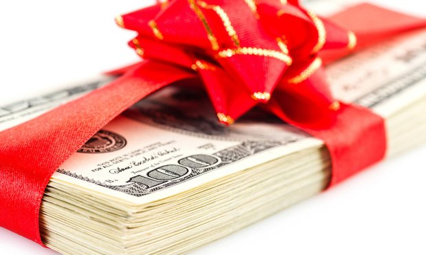 pile of $100 bills wrapped in a red bow