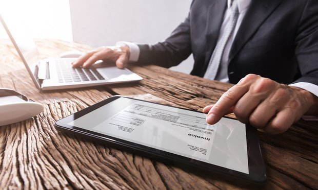 stock photo: Businessman working with invoice on digital tablet.