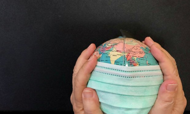 Putting a green surgical face mask on the globe sphere model.