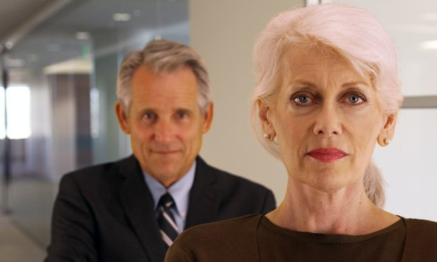 Older businesswoman with man behind her.