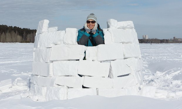 Cheerful woman resting in an incomplete igloo,Novosibirsk, Russia.