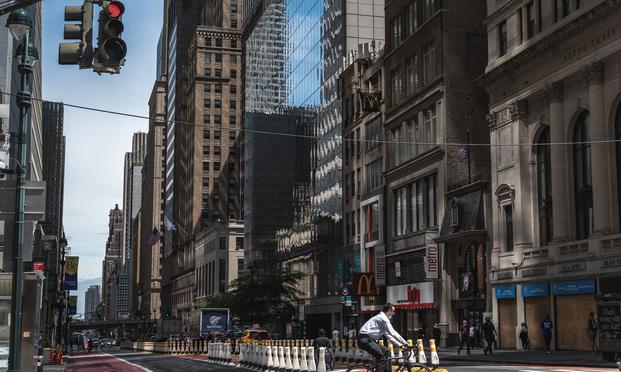 An office worker rides his bike through Midtown Manhattan in June. Photo: Ryland West/ALM