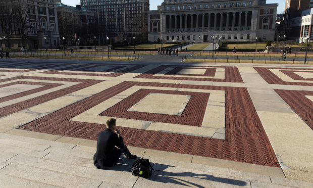 A man sits on the Columbia University campus, Monday, March 9, 2020, in New York. (AP Photo/Mark Lennihan)