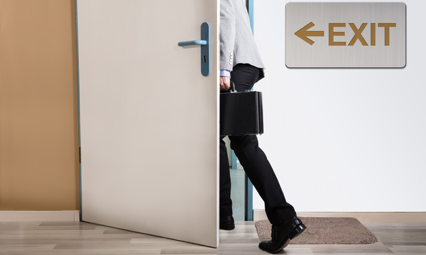 Businessman walking out with exit sign on wall/photo courtesy of Shutterstock