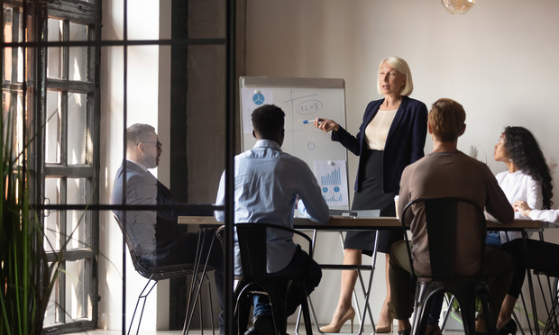 Mature older businesswoman mentor coach training speaker give flip chart business presentation at company meeting, confident female executive manager teaching team consult clients at office workshop.