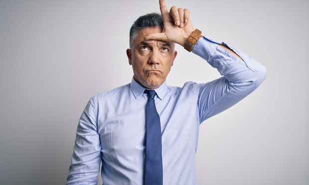 Middle age handsome grey-haired business man wearing elegant shirt and tie making fun of people with fingers on forehead doing loser gesture.