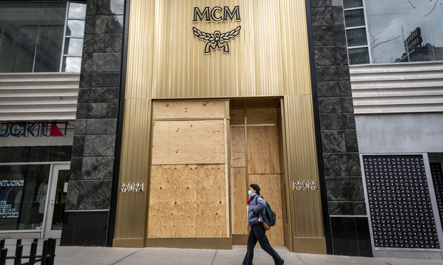 A pedestrian wearing a protective mask walks past a boarded up MCM store on Michigan Avenue in Chicago