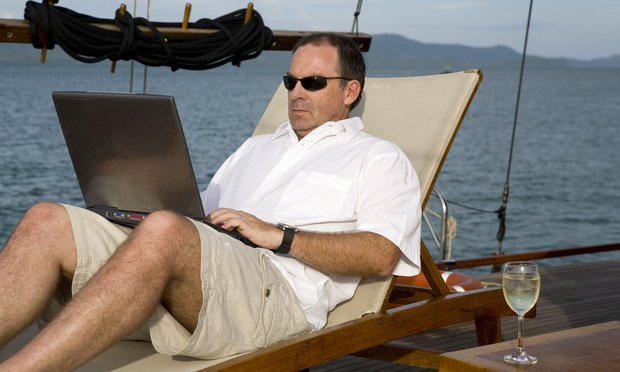 Businessman on deck of yacht with laptop.