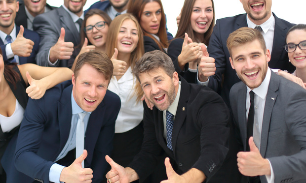 Jubilant business people giving thumbs up
