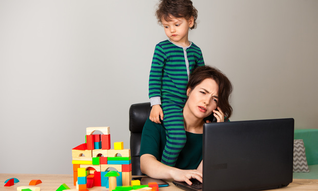 child on mother's shoulders as she wits at laptop working
