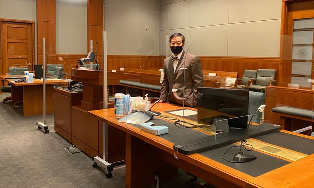 U.S. Magistrate Judge Tony Leung of the District of Minnesota in his courtroom showing counsel tables and podium aseparated by plexiglass, (Photo: Courtesy Photo)