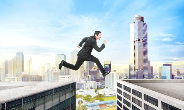 Businessman jumping over building gap on the city.