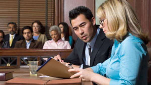 Woman attorney looking at note pad in courtroom with client
