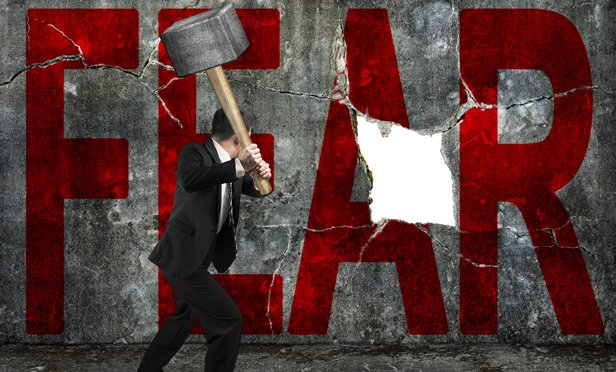 Businessman smashing fear with a hammer