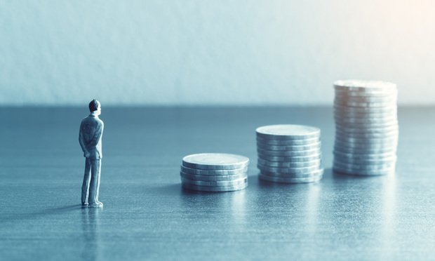 Miniature people standing with looking stack coin about financial and future money savings concept. - wutzkohphoto/Shuttertock
