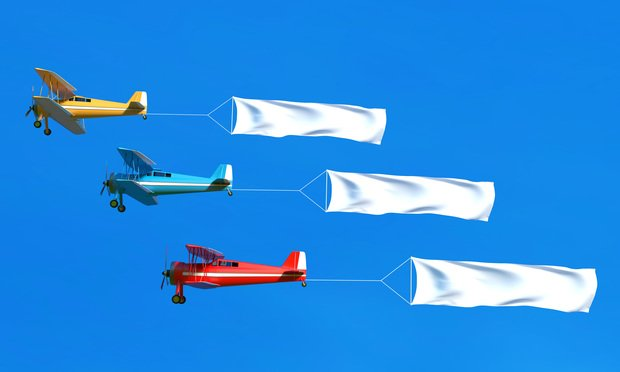Flying airplane and banner on blue sky.