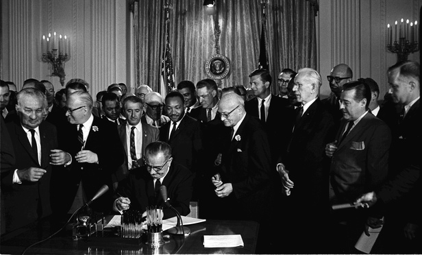 President Lyndon B. Johnson signs the 1964 Civil Rights Act as Martin Luther King, Jr., others look on.