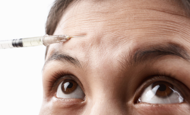 Woman face with botox injectionin forehead area