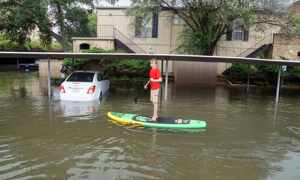 A teenager rides a paddle board in the flooded streets of Houston on Aug. 27, 2017.