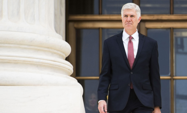 Associate Justice Neil Gorsuch walks down the steps of the U.S. Supreme Court after his Investiture ceremony on June 15, 2017.