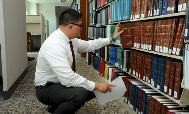 Raymond Withers-Tong, a law clerk, at the law library at Superior Court in New Britain, where the hours are being reduced due to budget issues.