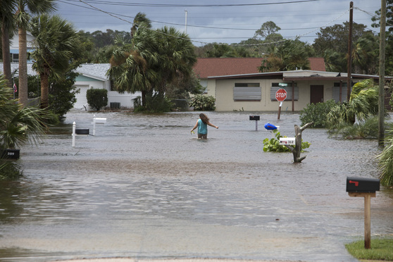 A woman walks in floodwaters in a Flagler County neighborhood after Hurricane Irma, Monday, Sept. 11, 2017. (Alex Menendez via AP)