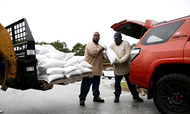Aut Smith, 42, and Willie Young, 52, load up sandbags for the community at the City of Gainesville Public Works Department, Wednesday, Sept. 6, 2017 in Gainesville, Fla. We are happy to be here helping people, said Young, who has been working for the city for 32 years. Irma roared into the Caribbean with record force early Wednesday, its 185-mph winds shaking homes and flooding buildings on a chain of small islands along a path toward Puerto Rico, Cuba and Hispaniola and a possible direct hit on densely populated South Florida. (Andrea Cornejo/The Gainesville Sun via AP)