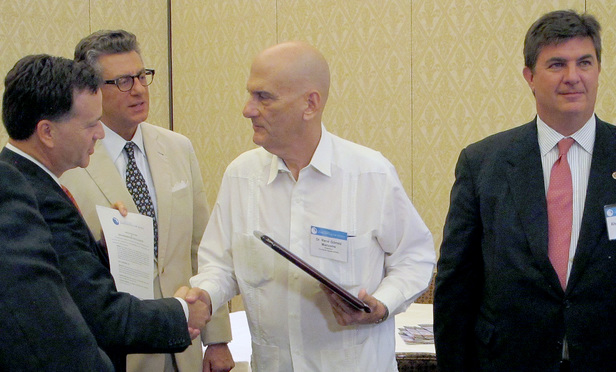 Cuban dissident and lawyer René de Jesús Gómez Manzano (center) receives an award from the Florida Bar's international section, represented by outgoing chair Peter Quinter (left), incoming chair Eduardo Palmer and secretary Alvin Lindsay. Gómez accepted the award Friday at the 2015 Annual Florida Bar Convention at the Boca Raton Resort & Club.