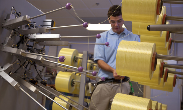 A DuPont technician examines Kevlar brand fibers. Kevlar, often used in vehicles and bullet-resistant body armor, is the centerpiece of trade-sectrets lawsuit DuPont filed in Virginia.