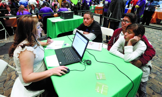 Enrollment counselor Nancy Gonzalez, left, helps the Alejo family, Hugo, left, his wife , Emedtiat and daughter Karla, 11, right, sign up for health insurance through the California's new health insurance exchange in Sacramento, Calif.