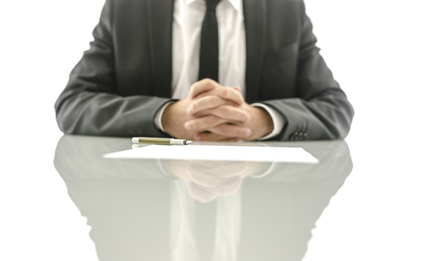 Front view of insurance agent sitting at his desk with papers and documents ready for his clients to sign them. Focus on a pen.