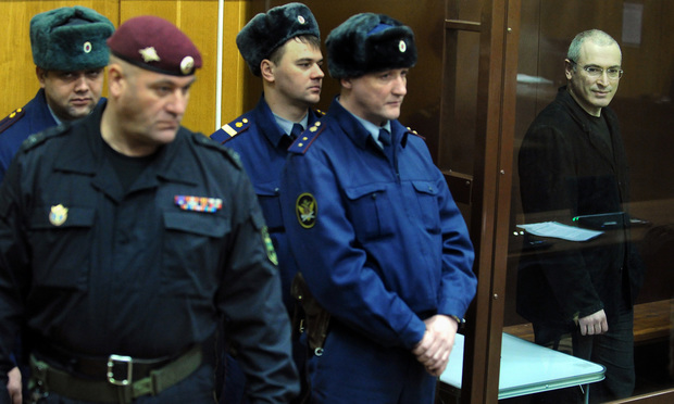 Yukos oil company chief executive officer Mikhail Khodorkovsky (R) stands behind a glass wall at a courtroom in Moscow, on December 29, 2010.