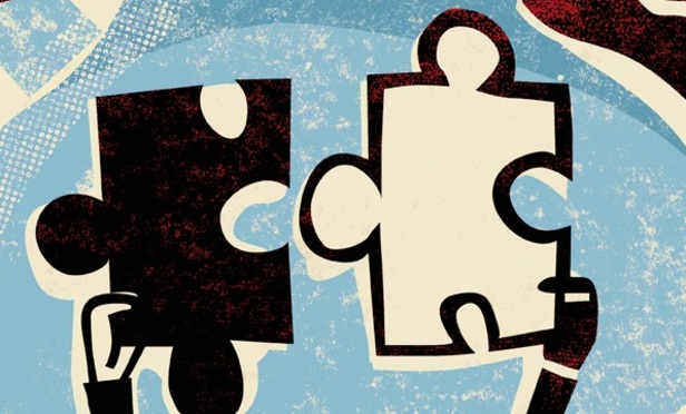 two businessmen joining puzzle pieces together, as they stand over buildings --- Image by © Images.com/Corbis
