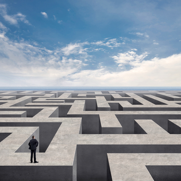 Rear view of businessman standing and looking on top of the labyrinth wall with sea and cloudy sky background. He is searching for the right way. Digitally generated image.