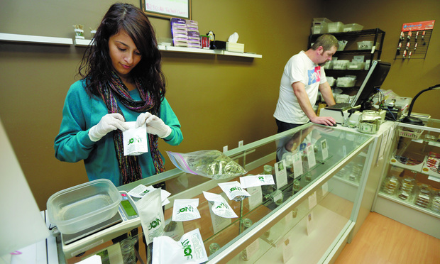 SMOKE: Employees of The Joint, a medical marijuana cooperative in Seattle, tend to patients.