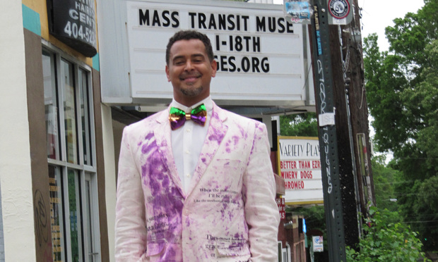 "Mike Molina, costumed in a fanciful take on a lawyer's white linen suit, portrays the main character in his new play, ""Mass Transit Muse."""