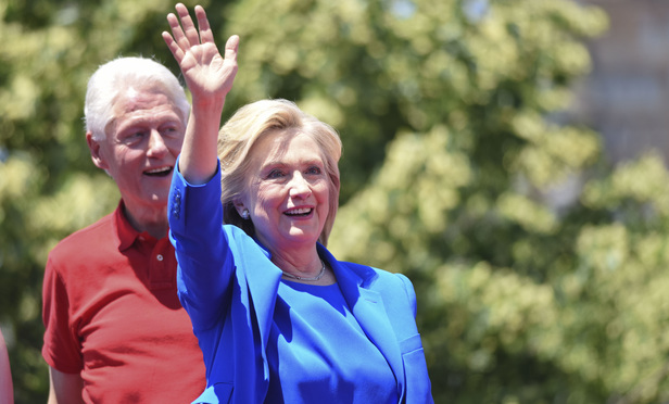 Hillary Clinton waves to supporters on Roosevelt Island after announcing she will seek the Democratic presidential nomination in 2016, while her husband, forrmer president Bill Clinton, watches from behind. June 13 2015.